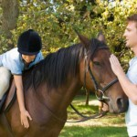Where is the best place to be positioned when teaching horse riding?